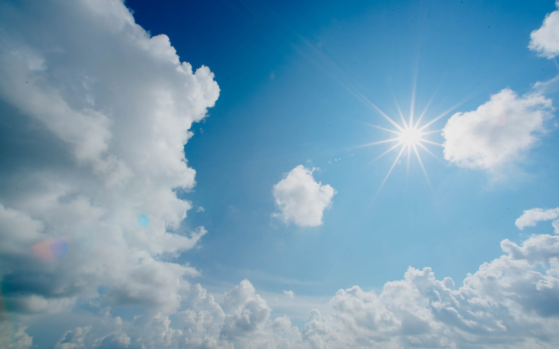 Sun shining in a blue sky with white clouds